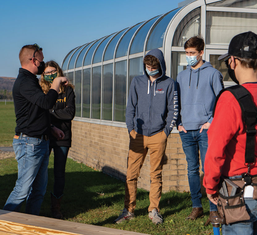 SUNY Morrisville faculty member Adam Olinski teaches Morrisville-Eaton Middle-High School students how to build raised garden beds at 18 their school.