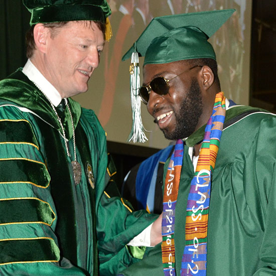President Rogers congratulates Charles Okine at commencement