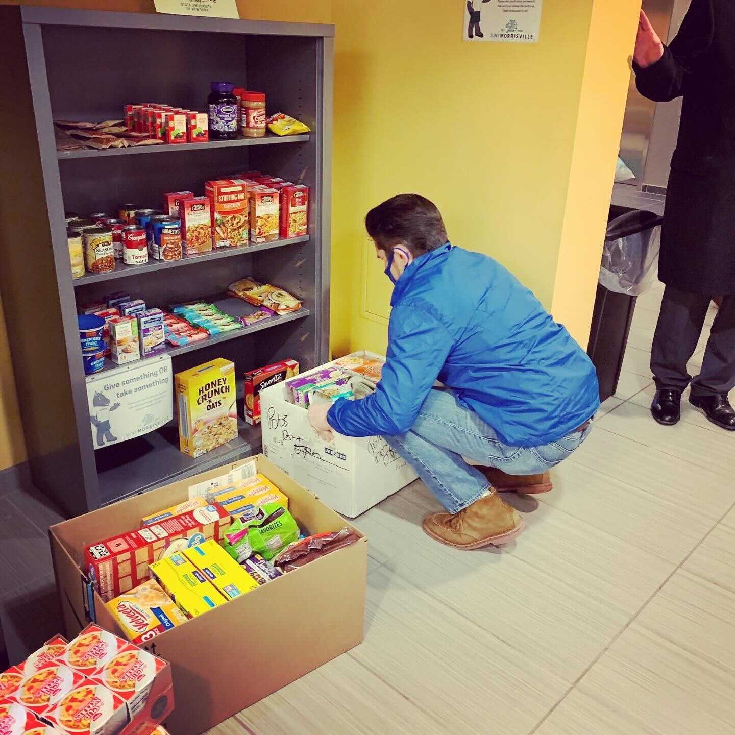 State University of New York Chancellor Jim Malatras visits SUNY Morrisville's campus food pantry and helps stock its shelves.