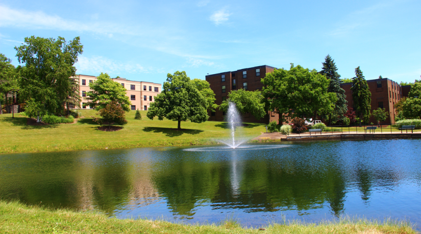 Residence halls overlooking a pond with a fountain.
