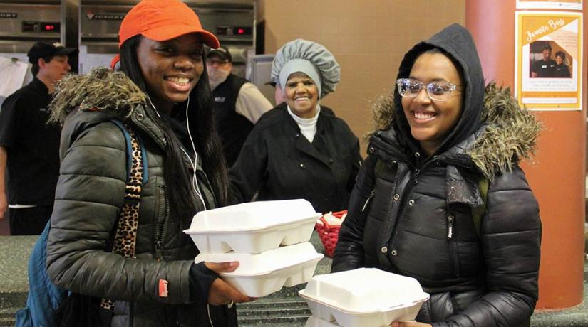 students holding takeout containers