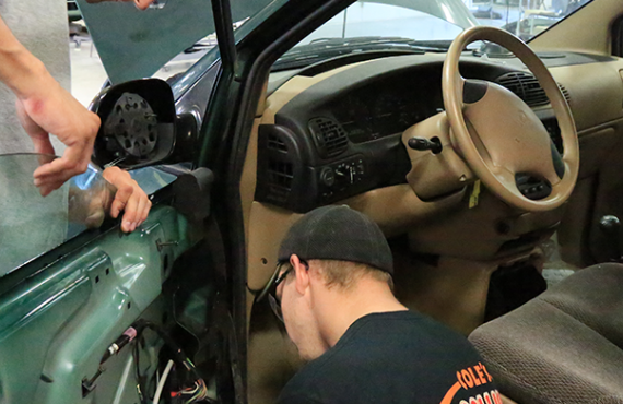 Auto body students working on a car