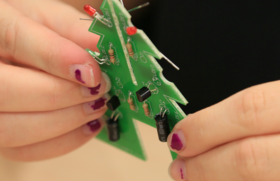 Close up of a student with a tiny circuit board