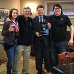 SUNY Morrisville President David Rogers (second from right), head brewer Micheal Coons (far right) and student Mary Cosenza (far left) were presented with a championship plaque by U.S. Open Beer Championships Director Dow Scoggins. Morrisville was named Grand National Champion of this year's competition (Photo credit Sarah Marcellus, MAC Associate Graphic Designer).